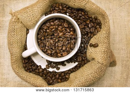 Coffee Beans Overflowing In Burlap Bag and White Ceramic Coffee Cup.  On Burlap Background