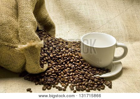 Coffee Beans Spilling Out of Burlap Bag and On White Ceramic Coffee Cup. Burlap Background