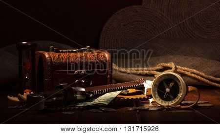 Old compass, treasure chest, hourglass, knife and money on a dark background.