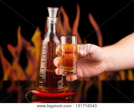 A bottle, a glass of pepper vodka in a man's hand and a hot red pepper on a background of flames.
