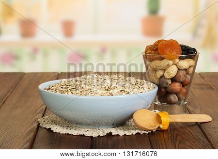 A bowl of oatmeal, nuts, dried fruit and a wooden spoon on a background of the kitchen.
