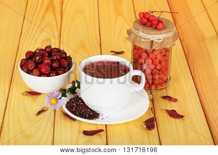 Autumn berries - rosehips, mountain ash and a cup of tea on a background of light wood.