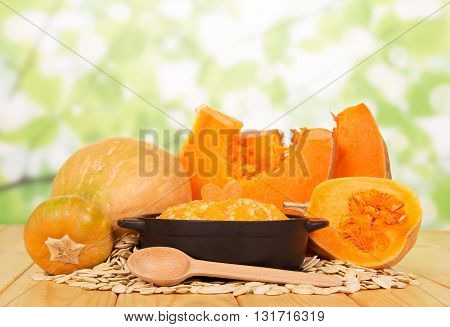 Saucepan porridge of rice and pumpkin seeds, wooden spoon on abstract green background.