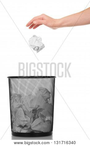 Hand throwing crumpled paper into a metal basket isolated on white background.