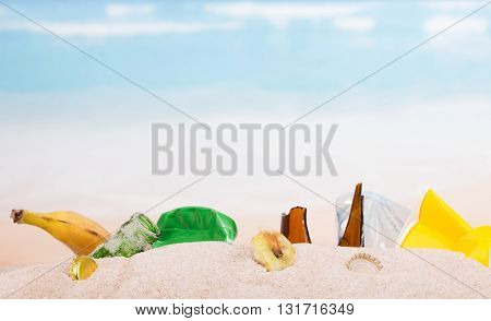 Leftovers, banana skins, plastic and glass bottles in the sand against the sea.