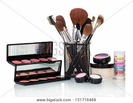 Cosmetic brush, eye shadow, blush and lip gloss isolated on white background.