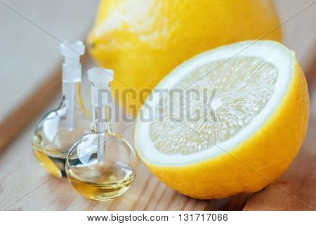 Essential aroma oil in glass bottle with fresh, juicy lemon fruit on wooden background. Beauty treatment. Spa concept. Selective focus.