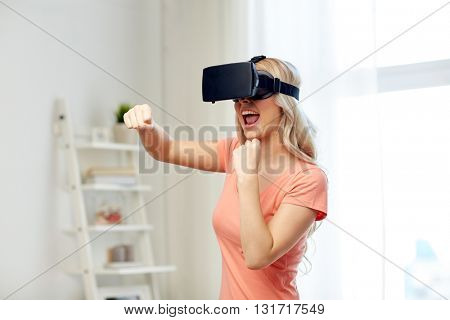 3d technology, virtual reality, entertainment and people concept - happy young woman with virtual reality headset or 3d glasses playing game and fighting at home