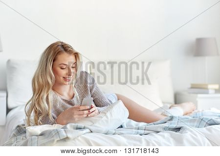 technology, communication and people concept - happy young woman lying in bed and texting on smartphone at home bedroom