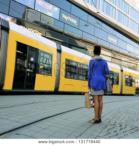 BERLIN, GERMANY - MAY 9, 2016: young woman waiting on the roadside at Alexanderplatz in Berlin and lets a tramway passing