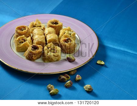 Arabic sweet. A middle eastern sweet 'Baklava' with few pistachio nuts on blue background.