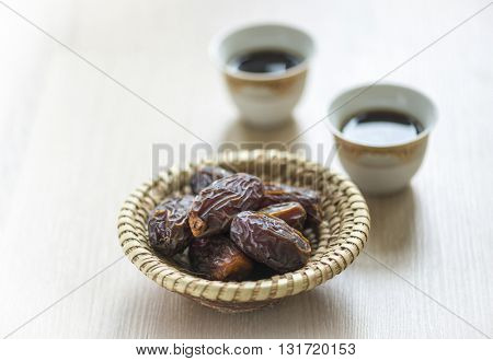Two cups of Arabic black coffee and dates in an earthen bowl.