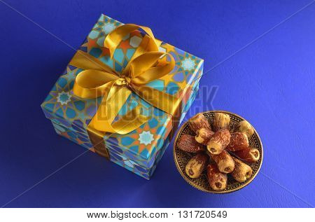 Islamic Festive Gift and dates. Bowl of Arabian dates with gift pack on blue background.