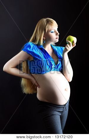 Portrait of a beautiful pregnant woman eating fresh apple. Over black background.