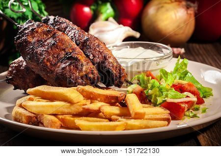 Grilled Shish Kebab Served With Fried Chips And Salad