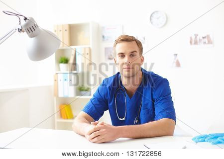 Portrait of skillful young veterinarian sitting at desk in his office. He is looking at camera with confidence