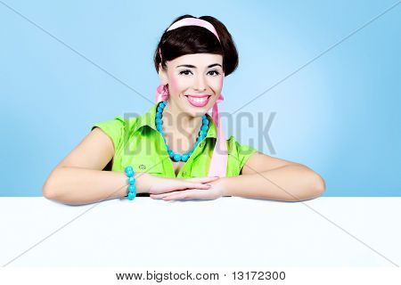 Portrait of a beautiful young woman in retro style holding white board.