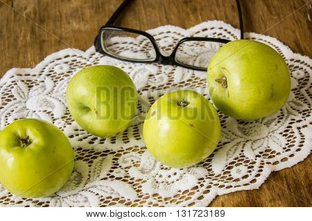 Green apples are medium in size and glasses with book on white lace napkin on a wooden table vintage