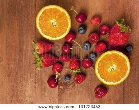 Bright fruits (oranges strawberries raspberries blueberries and cherries) on a dark wooden background texture with copyspace