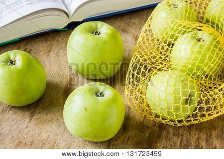 Green apples are medium in size on white lace napkin on a wooden table vintage