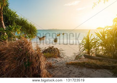 Beach with walk path in the morning sunshine day. Boats in the sea. Light filtered
