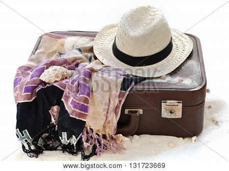 straw hat and sarong on suitcase in sand on white background