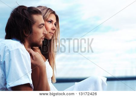 Beautiful young couple posing together over blue sky.