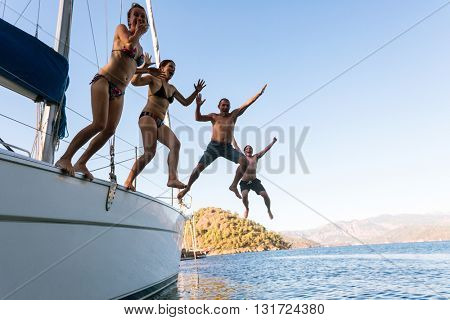 Young people jumping in water from yacht