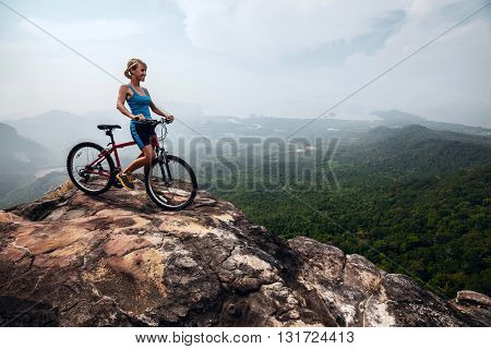 Young lady with bicycle standing on the top of mountain