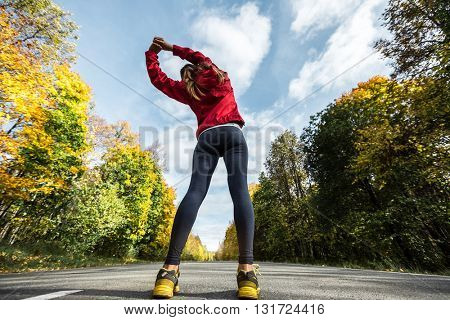Woman athlete makes exercise on an asphalt road in an autumn forest