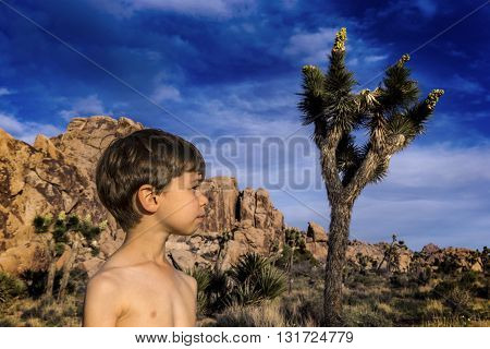 Boy in profile with a Yucca in Joshua Tree, mountains in the back.