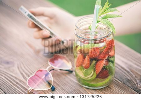 Girl using a cell phone outdoors, outdoor terrace.