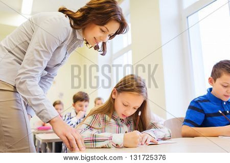 education, elementary school, learning and people concept - teacher helping school kids in classroom