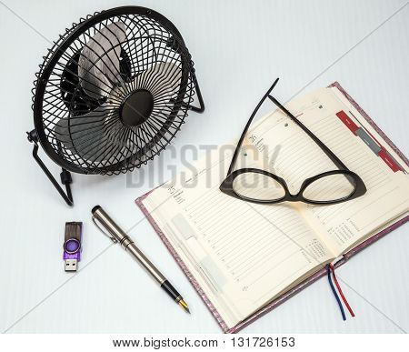 office tools blank notepad with pen glasses and table fan in the office desk.