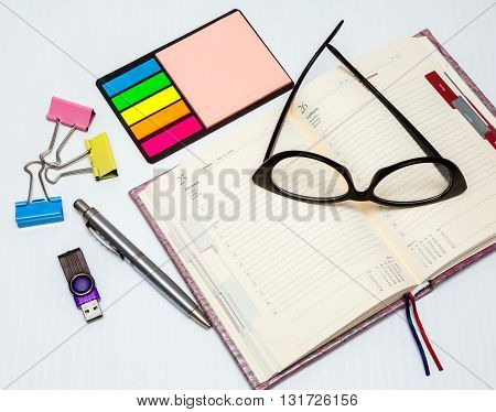 office tools blank notepad with pen glasses and flash card on office desk.