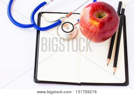 Red apple and stethoscope on notebook on a white background