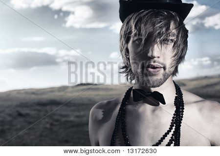 Fashion shot of a handsome young man posing topless in top hat and bow tie over beautiful landscape.