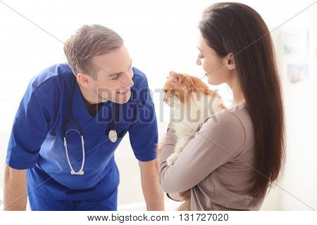 Pretty young woman is showing her cat to the veterinarian. She is standing and holding a pet. Man and woman are smiling