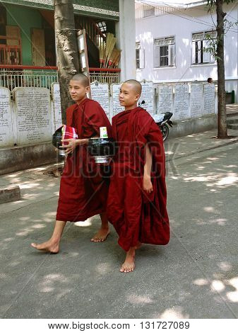 AMARAPURA, MYANMAR - APRIL 21 : young buddhist novices walk in Mahagandayon monastery on April 21, 2013 in Mandalay Myanmar (Burma)