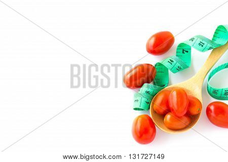 Red tometos in wooden spoon and measuring tape on a white background