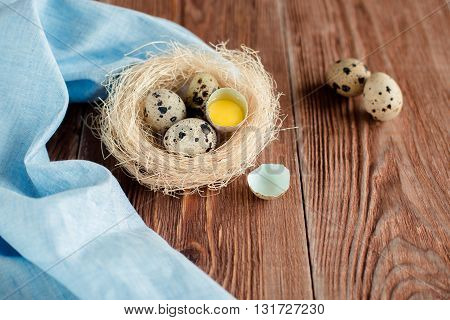 Brown wooden backgrond with nest with quail eggs and shell and blue napkin