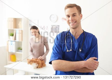 Waist up portrait of attractive young veterinarian standing and smiling. He is looking at camera with confidence. Pretty woman is preparing her cat for examination