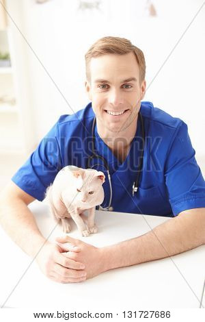 Skillful young vet is sitting at the desk near a cat sphinx. He is looking at camera and smiling
