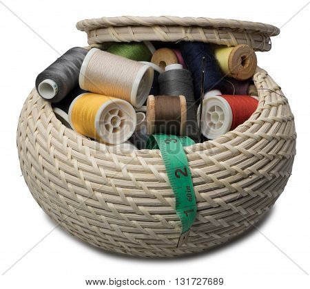 Wicker round box with accessories for needlework. Isolated on the white background. with shadow.