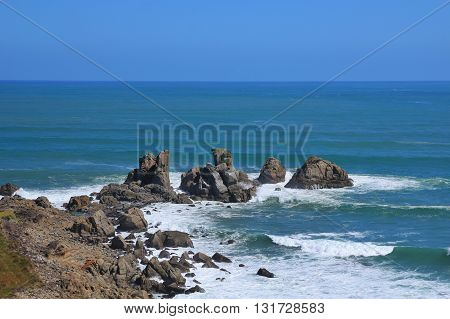 Scene at the west coast of New Zealand. Big rocks in the ocean.