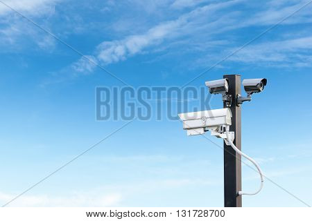 Security cctv surveillance camera over  blue sky with copy space