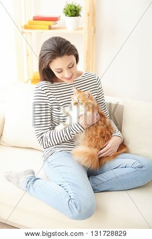 Beautiful young woman is holding a cat and stroking it with love. She is sitting on sofa and smiling