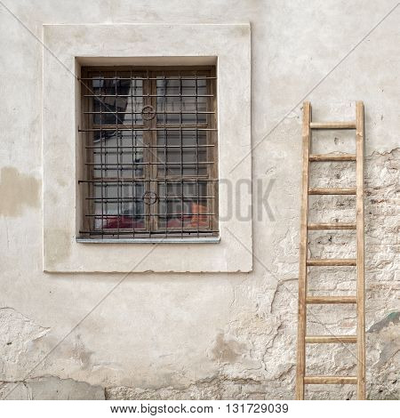abandoned grunge cracked brick stucco wall with a window grilles, weathered stucco wall with wooden ladder background