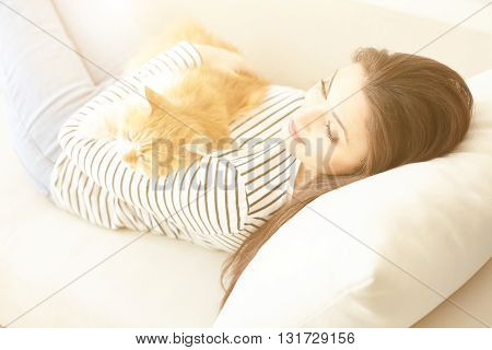 Attractive young girl is relaxing on sofa in the morning. She is lying and holding a cat. The lady is dreaming and smiling