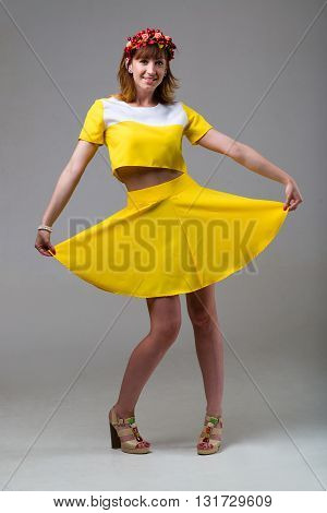 Young beautiful woman in yellow dress with red wreath on her head, dancing on gray backdround